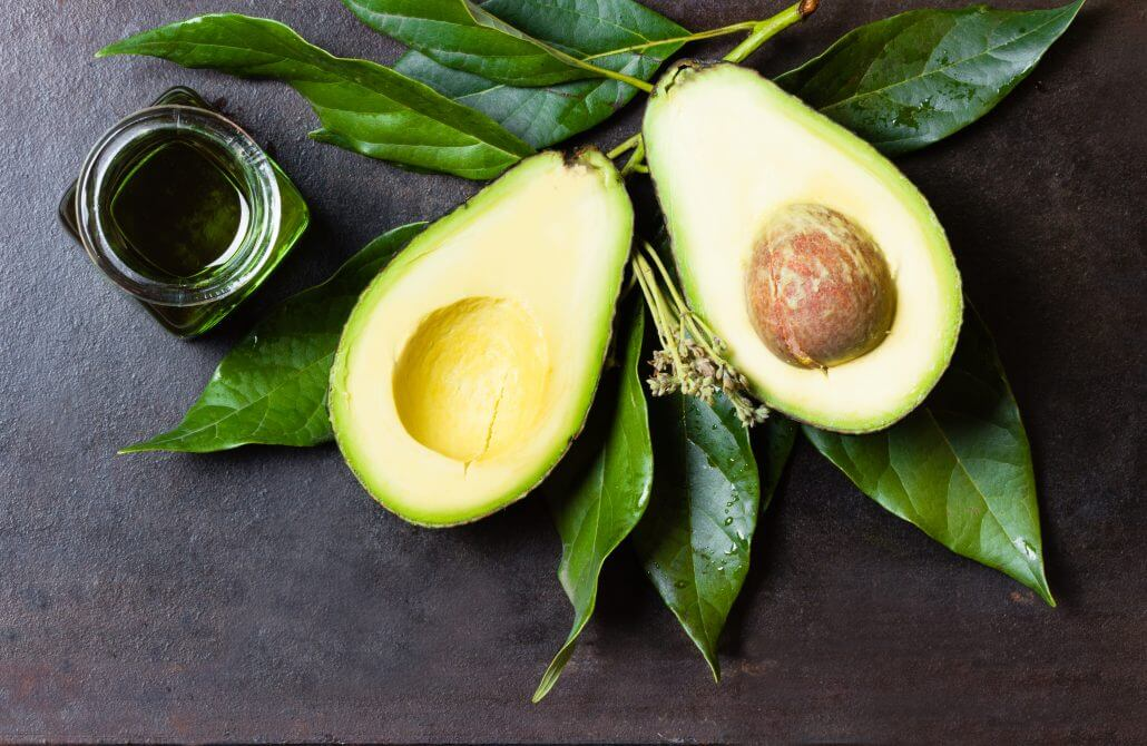 Avocado with leaves and jar of green oil. black background